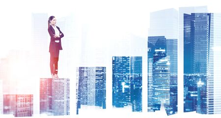 Beautiful young European businesswoman standing with crossed arms on bar chart with double exposure of blurry night cityscape. Concept of stock market and career success. Toned image