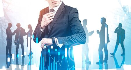 Unrecognizable trader looking at his watch in abstract city with his colleagues in background with double exposure of blurry digital chart. Concept of leadership and stock market. Toned image Imagens