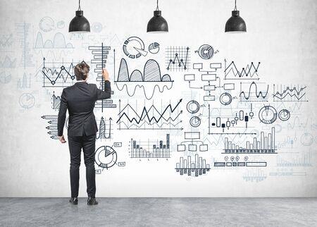 Rückansicht des jungen Geschäftsmannes, der Diagramme auf Betonwand im Raum mit drei Lampen zeichnet. Konzept des Finanzberichts und der Investition Standard-Bild