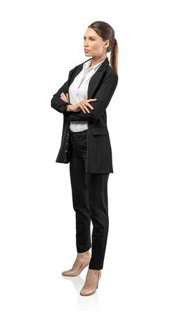 Isolated full length side portrait of serious young confident businesswoman with long fair hair standing with crossed arms. Concept of leadership and management Banque d'images