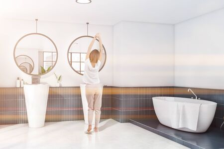 Rear view of young woman in pajamas standing in spacious bathroom with white and blue tiled walls, comfortable bathtub and double sink with two round mirrors. Toned image