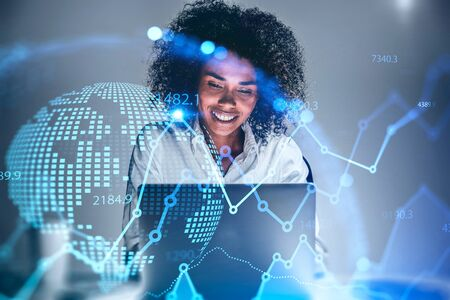 Cheerful young African American woman trader using laptop in blurry office with double exposure of blurry financial chart and planet hologram. Concept of stock market and technology. Toned image