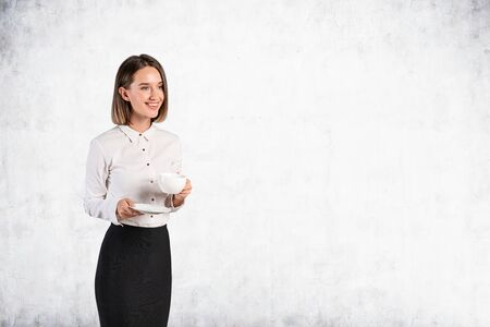 Portrait of smiling young European businesswoman holding cup and saucer and standing near concrete wall. Concept of coffee break and rest. Mock up