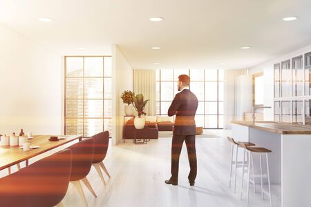 Young man in suit standing in panoramic open space kitchen with white walls, bar with stools, dining table with armchairs and living room with grey sofa in background. Blurry city. Toned image Foto de archivo