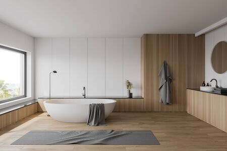 Interior of luxury bathroom with white and wooden walls, wooden floor, comfortable white bathtub and sink with round mirror. Window with blurry tropical view. 3d rendering Banco de Imagens