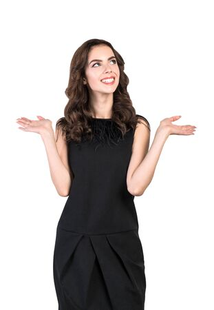 Isolated portrait of smiling young woman with wavy dark hair in black dress making choice. Concept of good options and advertising