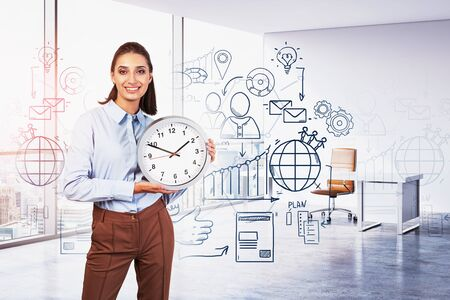 Cheerful young businesswoman holding clock in sunlit CEO office with double exposure of creative business plan sketch. Toned image