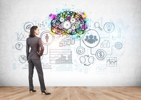 Rear view of confident young businesswoman looking at colorful brain sketch and business icons drawn on concrete wall. Concept of bright business idea