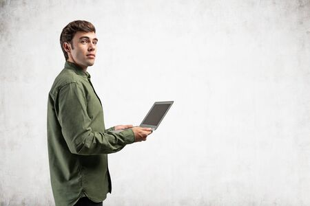 Side portrait of inspired young college student or computer guy in green shirt holding laptop near concrete wall. Concept of internet, communication and education. Mock up