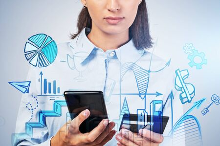 Portrait of unrecognizable young European businesswoman with smartphone and credit card standing near grey wall with double exposure of blue online shopping sketch. Concept of e commerce. Toned image