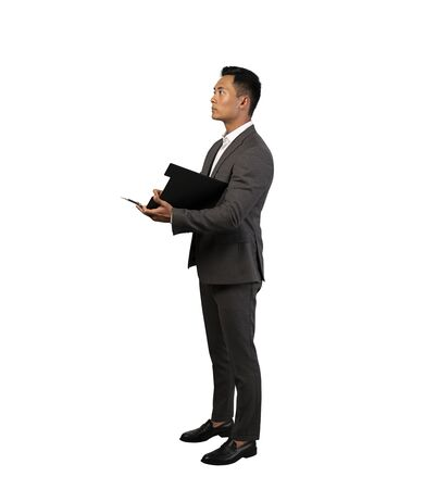 Isolated full length portrait of serious young Asian businessman holding clipboard. Concept of paperwork and leadership. Side view