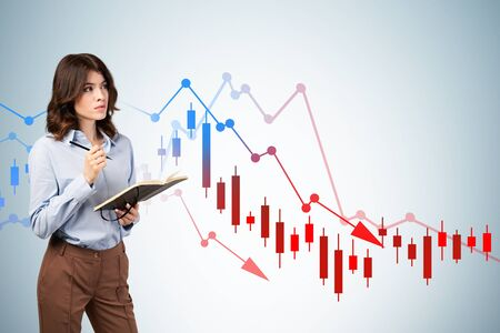 Thoughtful young European businesswoman with notebook and wavy brown hair standing near grey wall with falling graphs drawn on it. Concept of financial crisis and market crash