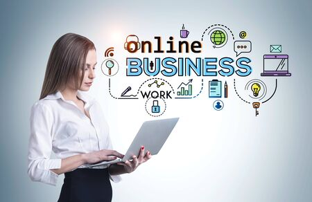 Young European businesswoman with fair hair using laptop near gray wall with colorful online business icons drawn on it. Concept of work during covid 19 coronavirus pandemic