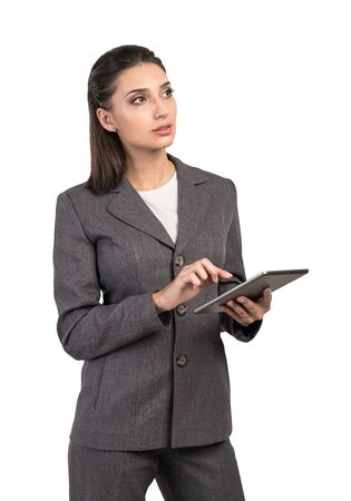Isolated portrait of pensive young businesswoman in elegant suit using tablet computer. Concept of technology and planning Banque d'images