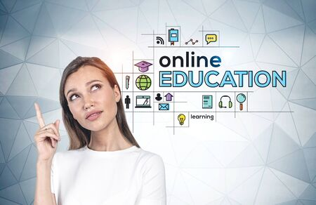 European young woman pointing upwards standing near grey wall with colorful online education icons. Concept of e learning during coronavirus covid 19 pandemic and bright idea