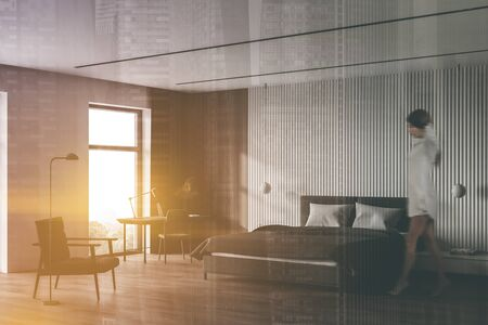 Blurry young woman walking in sunlit Scandinavian bedroom corner with white and wooden walls, comfortable king size bed and home office with computer table. Toned image double exposure