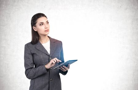 Portrait of pensive young businesswoman in elegant suit using tablet computer. Concept of technology and planning. Concrete wal background. Mock up Banque d'images