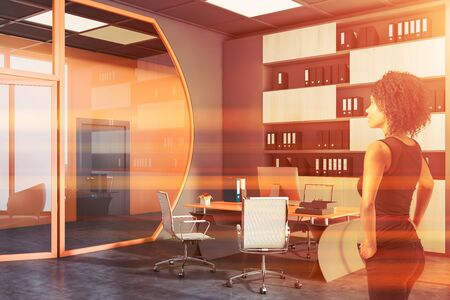 Confident young African American businesswoman standing in futuristic CEO office with bright orange and gray walls, computer table and bookcase with folders. Concept of leadership. Toned image