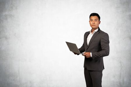 Half length portrait of serious young Asian businessman holding laptop near concrete wall. Concept of technology and corporate lifestyle. Mock up