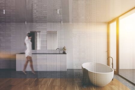 Blurry young woman walking in spacious sunlit bathroom with white walls, wooden floor, comfortable bathtub, double sink with mirrors and panoramic window. Toned image double exposure