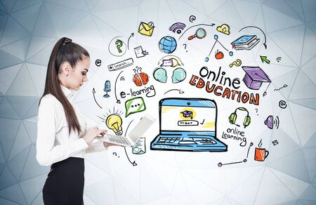 Side view of serious young businesswoman with laptop and long dark hair standing near grey wall with colorful online education sketch. Concept of e learning during coronavirus covid 19 pandemic