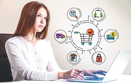 Pensive young woman with freckles using laptop at blurry table over beige background with creative and colorful shopping cart and online shopping icons. Toned image