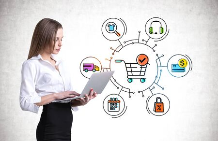 Young European businesswoman with fair hair using laptop near concrete wall with creative and colorful shopping cart and online shopping icons. Stockfoto