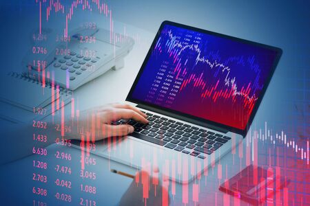 Hands of businessman using laptop at blurry office table with double exposure of falling financial chart. Concept of crisis and stock market. Toned image