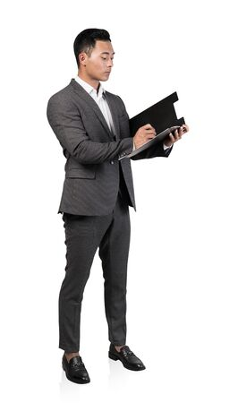 Isolated full length portrait of serious young Asian businessman writing on clipboard. Concept of paperwork and leadership