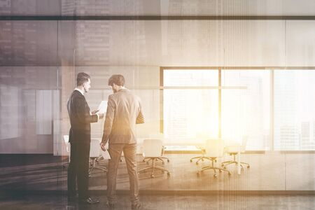 Two young businessmen discussing documents in panoramic business center hall with white meeting room with long conference table and blurry cityscape. Toned image double exposure
