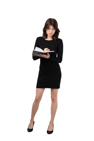 Isolated full length portrait of serious young businesswoman with dark hair wearing elegant black dress and taking notes. Concept of paperwork