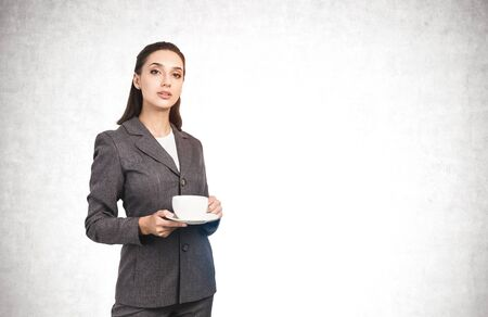 Portrait of beautiful young businesswoman in elegant suit holding white cup and saucer near concrete wall. Concept of coffee break and leadership. Mock up