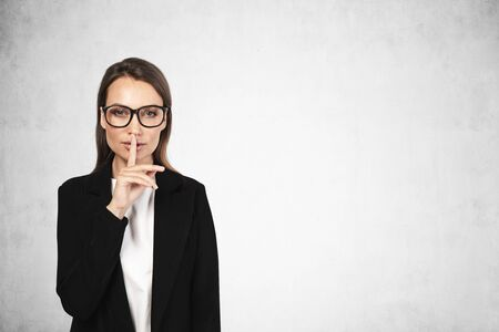 Portrait of beautiful young European businesswoman in glasses making hush sign near concrete wall. Concept of keeping a secret. Mock up