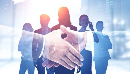 Close up of two businessmen shaking hands in blurry office with their teammates in background and double exposure of cityscape. Concept of partnership. Toned image Zdjęcie Seryjne
