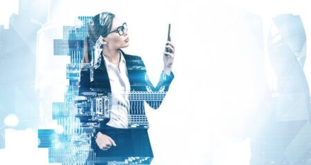 Beautiful young businesswoman in glasses using her smartphone with double exposure of blurry abstract cityscape. Concept of leadership and communication. Toned image