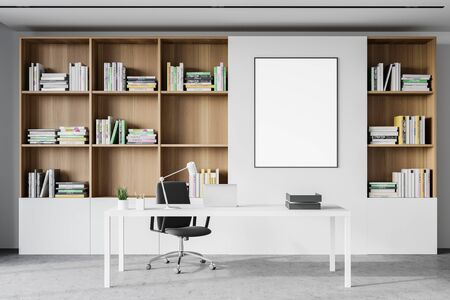 Interior of modern CEO office with white walls, concrete floor, computer table standing near bookcase and vertical mock up poster frame. 3d rendering Standard-Bild