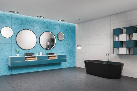 Corner of stylish bathroom with white and blue tiled walls, tiled floor, comfortable double sink standing on blue countertop with round mirrors and black bathtub. 3d rendering Banco de Imagens