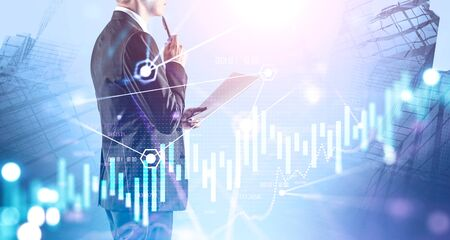 Unrecognizable thoughtful CEO working with document in abstract city with double exposure of blurry financial graph. Concept of leadership and stock market. Toned image Stock fotó
