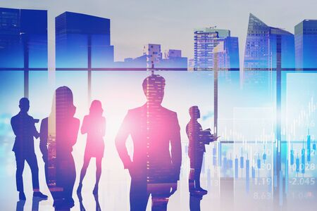 Silhouettes of business people in blurry panoramic office with double exposure of abstract cityscape and financial graph. Concept of stock market and investment. Toned image Foto de archivo