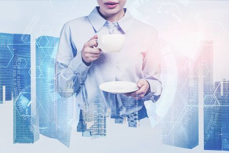 Unrecognizable businesswoman drinking coffee in smart city with double exposure of blurry immersive HUD interface. Concept of smart city and technology. Toned image