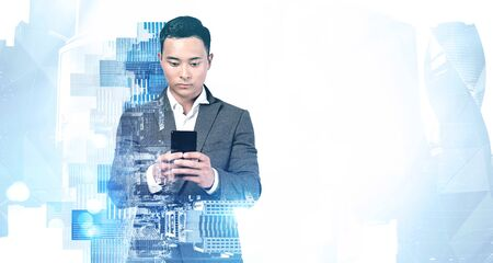 Portrait of serious young Asian businessman using his smartphone in blurry abstract city. Concept of communication and technology. Toned image double exposure