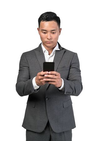 Isolated portrait of serious young Asian businessman using his smartphone. Concept of communication and technology