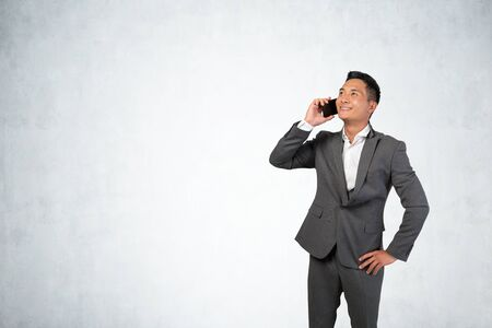 Portrait of smiling young Asian businessman talking on smartphone near concrete wall. Concept of communication and success. Mock up