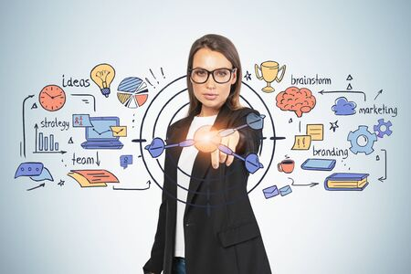 Beautiful young European businesswoman in glasses pointing at creative time for business sketch near gray wall. Concept of business planning and time management. Double exposure Zdjęcie Seryjne
