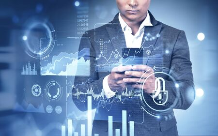 Unrecognizable young businessman using his smartphone in blurry office with double exposure of immersive digital infographic interface. Concept of market analysis and big data. Toned image