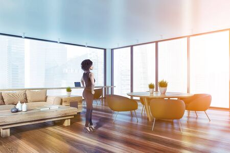 Attractive young African American woman standing in panoramic living room with beige sofa, coffee table, round dining table with brown armchairs and home office. Blurry cityscape window. Toned image