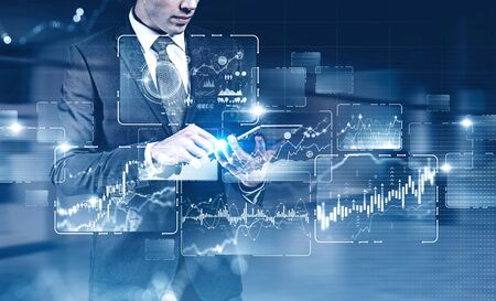 Unrecognizable young businessman with tablet working in blurry office with double exposure of immersive HUD business infographic interface. Toned image. Elements of this image furnished by NASA Zdjęcie Seryjne