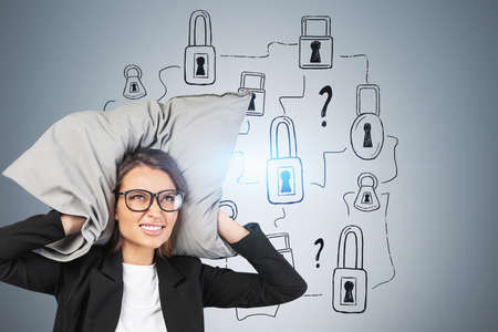 Portrait of stressed young businesswoman in glasses covering her ears with pillow near gray wall with padlocks and question marks drawn on it. Concept of looking for solution and problem solving