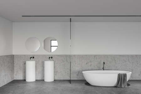 Interior of loft bathroom with white and stone walls, concrete floor, comfortable bathtub and double sink with two round mirrors. 3d rendering 版權商用圖片