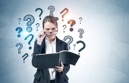 Portrait of confused young teacher reading in notebook near gray wall with question marks drawn on it. Concept of education and choice. Mock up Banque d'images - 150864457